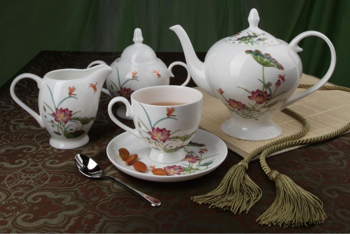 Чайный сервиз Royal Aurel Лотос арт.127, 15 предметовЧайные сервизы<br>Чайный сервиз Royal Aurel Лотос арт.127, 15 предметов<br><br><br><br><br><br><br><br><br><br><br>Чашка 270 мл,6 шт.<br>Блюдце 15 см,6 шт.<br>Чайник 1100 мл<br>Сахарница 370 мл<br><br><br><br><br><br><br><br><br>Молочник 300 мл<br><br><br><br><br><br><br><br><br>Производить посуду из фарфора начали в Китае на стыке 6-7 веков. Неустанно совершенствуя и селективно отбирая сырье для производства посуды из фарфора, мастерам удалось добиться выдающихся характеристик фарфора: белизны и тонкостенности. В XV веке появился особый интерес к китайской фарфоровой посуде, так как в это время Европе возникла мода на самобытные китайские вещи. Роскошный китайский фарфор являлся изыском и был в новинку, поэтому он выступал в качестве подарка королям, а также знатным людям. Такой дорогой подарок был очень престижен и по праву являлся элитной посудой. Как известно из многочисленных исторических документов, в Европе китайские изделия из фарфора ценились практически как золото. <br>Проверка изделий из костяного фарфора на подлинность <br>По сравнению с производством других видов фарфора процесс производства изделий из настоящего костяного фарфора сложен и весьма длителен. Посуда из изящного фарфора - это элитная посуда, которая всегда ассоциируется с богатством, величием и благородством. Несмотря на небольшую толщину, фарфоровая посуда - это очень прочное изделие. Для демонстрации плотности и прочности фарфора можно легко коснуться предметов посуды из фарфора деревянной палочкой, и тогда мы услушим характерный металлический звон. В составе фарфоровой посуды присутствует костяная зола, благодаря чему она может быть намного тоньше (не более 2,5 мм) и легче твердого или мягкого фарфора. Безупречная белизна - ключевой признак отличия такого фарфора от других. Цвет обычного фарфора сероватый или ближе к голубоватому, а костяной фарфор будет всегда будет молочно-белого цвета. Характерная и немаловажная деталь - это невесом