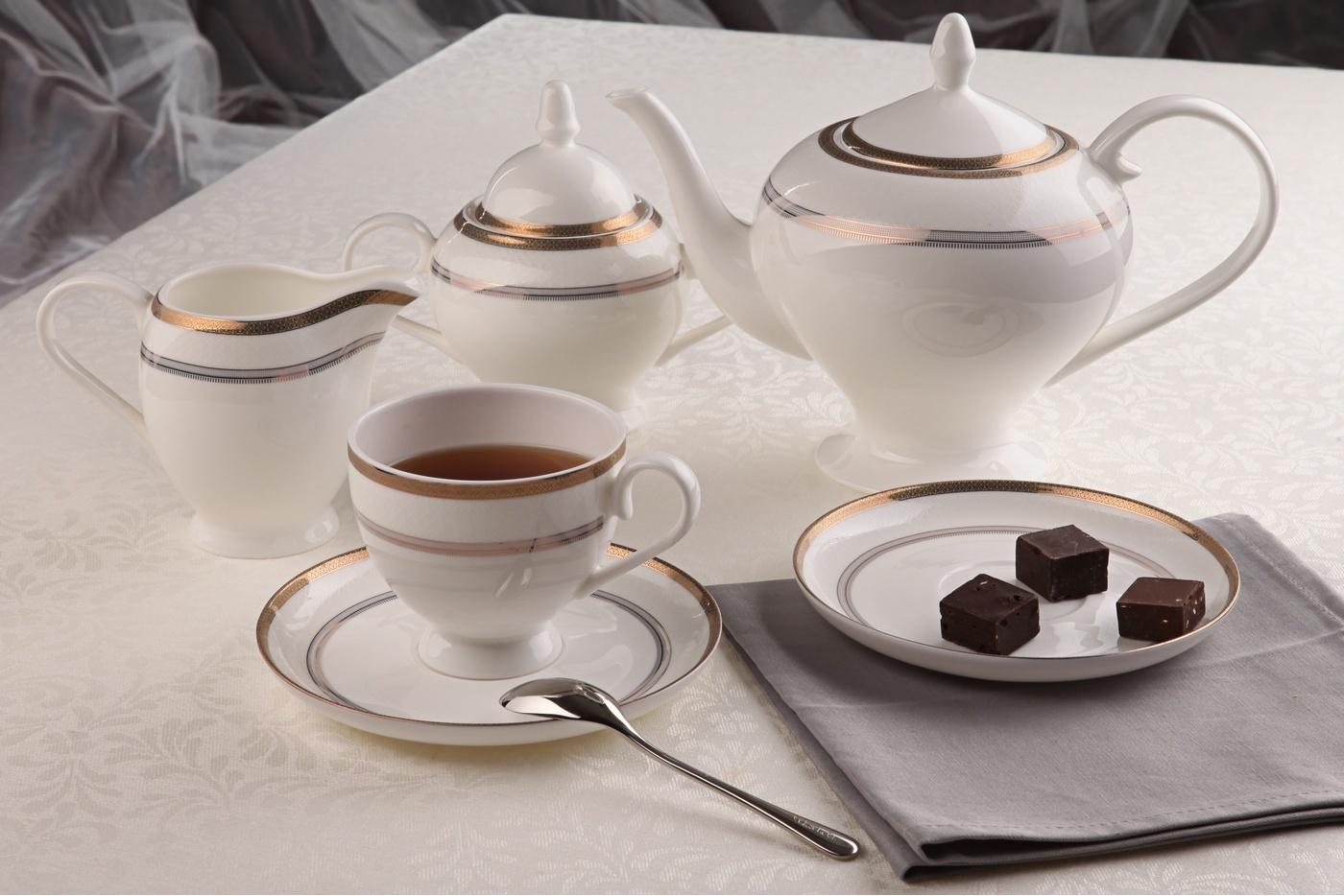 Чайный сервиз Royal Aurel Консул арт.103, 15 предметовЧайные сервизы<br>Чайныйсервиз Royal Aurel Консул арт.103, 15предметов<br><br><br><br><br><br><br><br><br><br><br><br>Чашка 270 мл,6 шт.<br>Блюдце 15 см,6 шт.<br>Чайник 1100 мл<br>Сахарница 370 мл<br><br><br><br><br><br><br><br><br>Молочник 300 мл<br><br><br><br><br><br><br><br><br>Производить посуду из фарфора начали в Китае на стыке 6-7 веков. Неустанно совершенствуя и селективно отбирая сырье для производства посуды из фарфора, мастерам удалось добиться выдающихся характеристик фарфора: белизны и тонкостенности. В XV веке появился особый интерес к китайской фарфоровой посуде, так как в это время Европе возникла мода на самобытные китайские вещи. Роскошный китайский фарфор являлся изыском и был в новинку, поэтому он выступал в качестве подарка королям, а также знатным людям. Такой дорогой подарок был очень престижен и по праву являлся элитной посудой. Как известно из многочисленных исторических документов, в Европе китайские изделия из фарфора ценились практически как золото. <br>Проверка изделий из костяного фарфора на подлинность <br>По сравнению с производством других видов фарфора процесс производства изделий из настоящего костяного фарфора сложен и весьма длителен. Посуда из изящного фарфора - это элитная посуда, которая всегда ассоциируется с богатством, величием и благородством. Несмотря на небольшую толщину, фарфоровая посуда - это очень прочное изделие. Для демонстрации плотности и прочности фарфора можно легко коснуться предметов посуды из фарфора деревянной палочкой, и тогда мы услушим характерный металлический звон. В составе фарфоровой посуды присутствует костяная зола, благодаря чему она может быть намного тоньше (не более 2,5 мм) и легче твердого или мягкого фарфора. Безупречная белизна - ключевой признак отличия такого фарфора от других. Цвет обычного фарфора сероватый или ближе к голубоватому, а костяной фарфор будет всегда будет молочно-белого цвета. Характерная и немаловажная деталь - это нев
