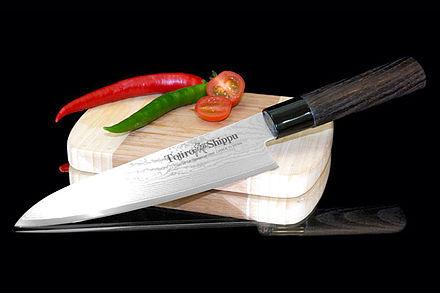 Нож кухонный стальной Шеф (180мм) Tojiro Shippu FD-593Tojiro Shippu<br>Нож кухонный стальной Шеф (180мм) Tojiro Shippu FD-593<br><br>Ножи Tojiro Shippu – профессиональные японские ножи! Это сочетание классического дизайна и современных материалов и технологий. Рисунок дамасковых обкладок спокойный, границы между слоями немного чувствуются. Граница перехода накладок к центральному слою аккуратная, с обоих сторон.<br>Центральный слой из японской стали VGold-10 дает отличный рез и длительную остроту.Серия ножей с рукоятками из натурального дерева и дамасскими клинками. Это поистине триумф японской гармонии на вашей кухне. Сердцевину клинка с твердостью до 63 HRc защищает обкладка из 37 или 63 слоев нержавеющей стали.<br>Серия кухонных ножей Tojiro Shippu - это серия ножей класса Люкс - элегантных японских ножей из дамасской стали.<br>Официальный сертифицированный продавец TOJIRO<br>