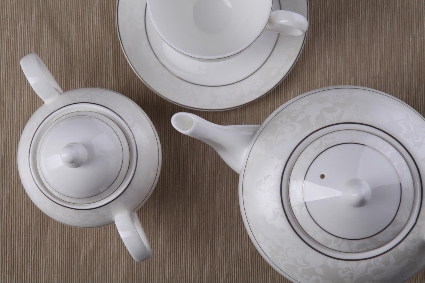 Чайный сервиз Royal Aurel Пион белый арт.105, 15 предметовЧайные сервизы<br>Чайныйсервиз Royal Aurel Пион белый арт.105, 15предметов<br><br><br><br><br><br><br><br><br><br><br><br>Чашка 270 мл,6 шт.<br>Блюдце 15 см,6 шт.<br>Чайник 1100 мл<br>Сахарница 370 мл<br><br><br><br><br><br><br><br><br>Молочник 300 мл<br><br><br><br><br><br><br><br><br>Производить посуду из фарфора начали в Китае на стыке 6-7 веков. Неустанно совершенствуя и селективно отбирая сырье для производства посуды из фарфора, мастерам удалось добиться выдающихся характеристик фарфора: белизны и тонкостенности. В XV веке появился особый интерес к китайской фарфоровой посуде, так как в это время Европе возникла мода на самобытные китайские вещи. Роскошный китайский фарфор являлся изыском и был в новинку, поэтому он выступал в качестве подарка королям, а также знатным людям. Такой дорогой подарок был очень престижен и по праву являлся элитной посудой. Как известно из многочисленных исторических документов, в Европе китайские изделия из фарфора ценились практически как золото. <br>Проверка изделий из костяного фарфора на подлинность <br>По сравнению с производством других видов фарфора процесс производства изделий из настоящего костяного фарфора сложен и весьма длителен. Посуда из изящного фарфора - это элитная посуда, которая всегда ассоциируется с богатством, величием и благородством. Несмотря на небольшую толщину, фарфоровая посуда - это очень прочное изделие. Для демонстрации плотности и прочности фарфора можно легко коснуться предметов посуды из фарфора деревянной палочкой, и тогда мы услушим характерный металлический звон. В составе фарфоровой посуды присутствует костяная зола, благодаря чему она может быть намного тоньше (не более 2,5 мм) и легче твердого или мягкого фарфора. Безупречная белизна - ключевой признак отличия такого фарфора от других. Цвет обычного фарфора сероватый или ближе к голубоватому, а костяной фарфор будет всегда будет молочно-белого цвета. Характерная и немаловажная деталь -