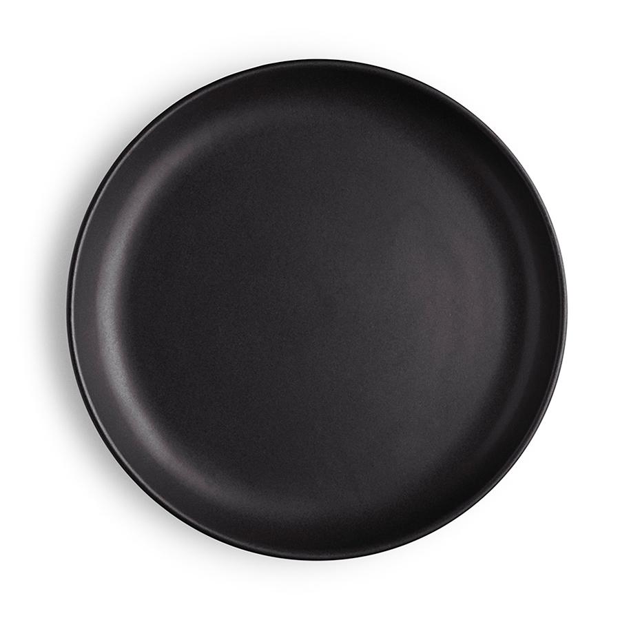 Блюдо Eva Solo Nordic Kitchen D20 см 502789Блюда<br>Блюдо Eva Solo Nordic Kitchen D20 см 502789<br><br>Минималистичный дизайн и высокая функциональность составляют суть скандинавского дизайна. Коллекция предметов сервировки из керамики коллекции Nordic kitchen воплотила все черты скандинавской эстетики. Простой выверенный дизайн черной каменной керамики в рустикальном скандинавском стиле.  На тарелке с плоским дном и закруглёнными бортиками удобно сервировать небольшие закуски и десерты. Чёрное матовое покрытие подчёркивает яркие цвета соусов, фруктов, овощей и зелени. Тарелку можно использовать в духовке, морозильной камере, микроволновой печи и мыть в посудомоечной машине.<br>