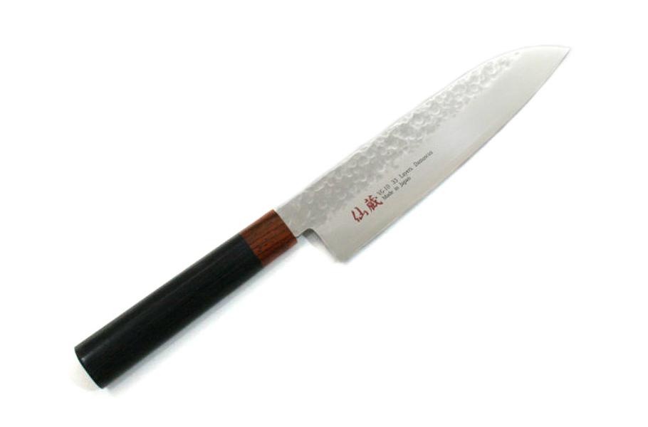 Нож кухонный стальной Сантоку (180мм) Suncraft Senzo 1012-02Suncraft Senzo<br>Нож кухонный стальной Сантоку (180мм) Suncraft Senzo 1012-02<br><br>Нож Cантоку Suncraft 1012-02 переназначен для нарезки, рубки, шинковки и чистки различных продуктов: мяса, овощей, фруктов, колбас и сыров. Имеет лаконичный дизайн и универсален в использовании. Волнистые очертания по бокам одного из самых массивных ножей берут свои истоки от прародителей данной модели – древнего самурайского оружия, славящегося на весь мир непревзойденной остротой лезвия. Одним из преимуществ ножа Cантоку является ручная работа, доказательством которой служит клеймо мастера на срезе каждого экземпляра.<br>Внешний вид инструмента напоминает топорик, его тыльная сторона имеет округленную форму книзу и прямую режущую кромку. Благодаря смещенному центру тяжести ножа вперед и широкому лезвию облегчается процесс нарезки, что особенно удобно при шинковке овощей и нарезки сашими или суши.<br>За основу рукояти взят материал пакка – дерево, предварительно обработанное смолами. Ненавязчивые цвета рукояти подчеркивают изящность данной модели.<br>Клинок ножа серии Senzo очень прочный и острый благодаря специальной технологии изготовления металла. Антикоррозийная высокоуглеродистая сталь V-Gold 10, содержащая кобальт и молибден, окружена слоями из более мягкой нержавеющей стали в 33 слоя. Благодаря Дамасской стали нож 1012-02 имеет острое и не теряющее заточку лезвие. Именно такая конструкция позволяет ему оставаться всегда острым и сохранять в продуктах максимальное количество полезных веществ.<br>Нож нельзя мыть в посудомоечной машине. Если на лезвии появились потемнения, используйте для чистки средства, не содержащие хлор и абразивные частицы. Чтобы предотвратить их появление, всегда насухо вытирайте нож после использования.<br>