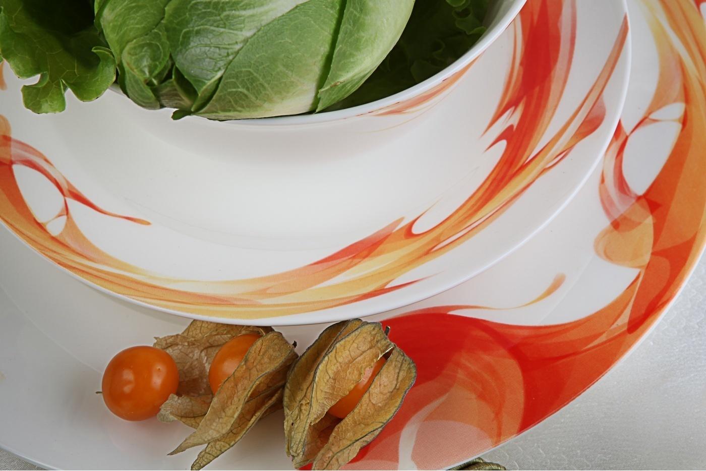 Столовый сервиз Royal Aurel Фиеста арт.435, 27 предметовСтоловые сервизы<br>Столовый сервиз Royal Aurel Фиеста арт.435, 27 предметов<br><br><br><br><br><br><br><br><br><br><br><br>Тарелка плоская 27 см, 6 шт.<br>Тарелка плоская 20 см, 6 шт.<br>Тарелка суповая 19,5 см, 6 шт.<br>Салатник 15 см, 6 шт.<br><br><br><br><br><br><br><br><br>Блюдо овальное 31см<br>Солонка и перечница<br><br><br><br><br><br><br><br>Производить посуду из фарфора начали в Китае на стыке 6-7 веков. Неустанно совершенствуя и селективно отбирая сырье для производства посуды из фарфора, мастерам удалось добиться выдающихся характеристик фарфора: белизны и тонкостенности. В XV веке появился особый интерес к китайской фарфоровой посуде, так как в это время Европе возникла мода на самобытные китайские вещи. Роскошный китайский фарфор являлся изыском и был в новинку, поэтому он выступал в качестве подарка королям, а также знатным людям. Такой дорогой подарок был очень престижен и по праву являлся элитной посудой. Как известно из многочисленных исторических документов, в Европе китайские изделия из фарфора ценились практически как золото. <br>Проверка изделий из костяного фарфора на подлинность <br>По сравнению с производством других видов фарфора процесс производства изделий из настоящего костяного фарфора сложен и весьма длителен. Посуда из изящного фарфора - это элитная посуда, которая всегда ассоциируется с богатством, величием и благородством. Несмотря на небольшую толщину, фарфоровая посуда - это очень прочное изделие. Для демонстрации плотности и прочности фарфора можно легко коснуться предметов посуды из фарфора деревянной палочкой, и тогда мы услушим характерный металлический звон. В составе фарфоровой посуды присутствует костяная зола, благодаря чему она может быть намного тоньше (не более 2,5 мм) и легче твердого или мягкого фарфора. Безупречная белизна - ключевой признак отличия такого фарфора от других. Цвет обычного фарфора сероватый или ближе к голубоватому, а костяной фарфор будет всегда