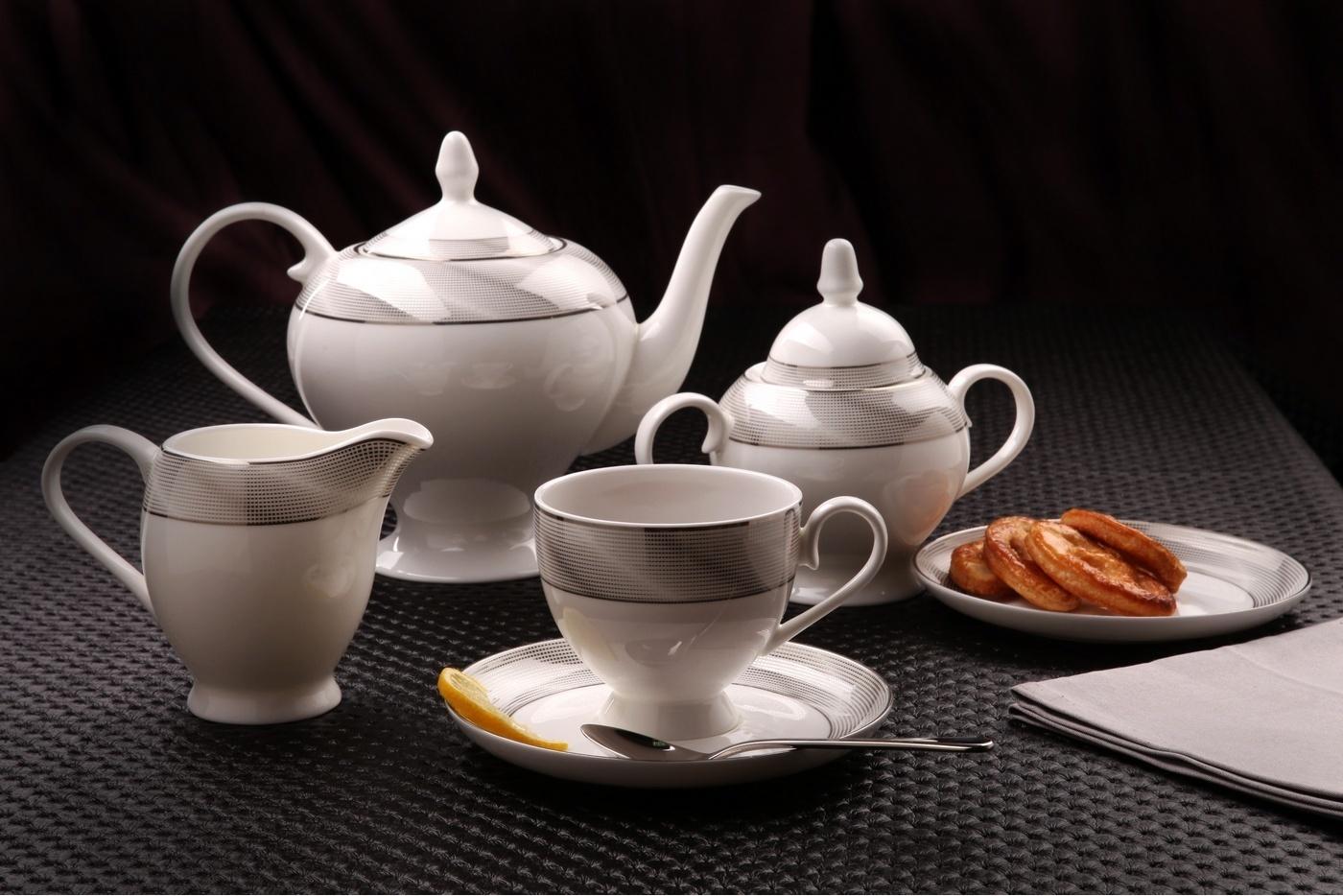 Чайный сервиз Royal Aurel Серебро арт.115, 15 предметовЧайные сервизы<br>Чайный сервиз Royal Aurel Серебро арт.115, 15 предметов<br><br><br><br><br><br><br><br><br><br><br>Чашка 270 мл,6 шт.<br>Блюдце 15 см,6 шт.<br>Чайник 1100 мл<br>Сахарница 370 мл<br><br><br><br><br><br><br><br><br>Молочник 300 мл<br><br><br><br><br><br><br><br><br>Производить посуду из фарфора начали в Китае на стыке 6-7 веков. Неустанно совершенствуя и селективно отбирая сырье для производства посуды из фарфора, мастерам удалось добиться выдающихся характеристик фарфора: белизны и тонкостенности. В XV веке появился особый интерес к китайской фарфоровой посуде, так как в это время Европе возникла мода на самобытные китайские вещи. Роскошный китайский фарфор являлся изыском и был в новинку, поэтому он выступал в качестве подарка королям, а также знатным людям. Такой дорогой подарок был очень престижен и по праву являлся элитной посудой. Как известно из многочисленных исторических документов, в Европе китайские изделия из фарфора ценились практически как золото. <br>Проверка изделий из костяного фарфора на подлинность <br>По сравнению с производством других видов фарфора процесс производства изделий из настоящего костяного фарфора сложен и весьма длителен. Посуда из изящного фарфора - это элитная посуда, которая всегда ассоциируется с богатством, величием и благородством. Несмотря на небольшую толщину, фарфоровая посуда - это очень прочное изделие. Для демонстрации плотности и прочности фарфора можно легко коснуться предметов посуды из фарфора деревянной палочкой, и тогда мы услушим характерный металлический звон. В составе фарфоровой посуды присутствует костяная зола, благодаря чему она может быть намного тоньше (не более 2,5 мм) и легче твердого или мягкого фарфора. Безупречная белизна - ключевой признак отличия такого фарфора от других. Цвет обычного фарфора сероватый или ближе к голубоватому, а костяной фарфор будет всегда будет молочно-белого цвета. Характерная и немаловажная деталь - это нев