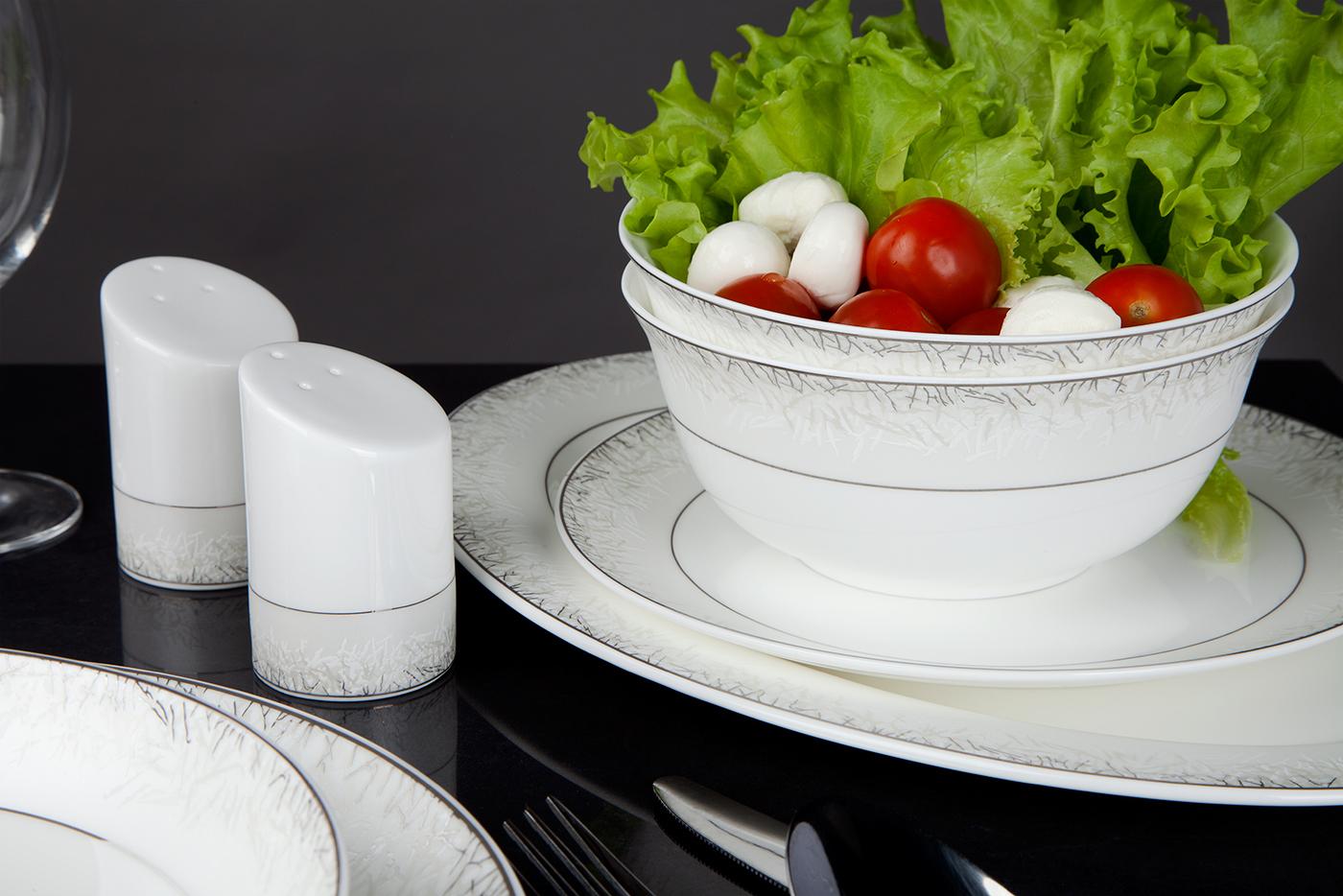Столовый сервиз Royal Aurel Иней на 27 предметов арт. 310Столовые сервизы<br>Столовый сервиз Royal Aurel Иней арт.310, 27 предметов<br><br><br><br><br><br><br><br><br><br><br><br>Тарелка плоская 25,5 см, 6 шт.<br>Тарелка плоская 20 см, 6 шт.<br>Тарелка суповая 19,5 см, 6 шт.<br>Салатник 15 см, 6 шт.<br><br><br><br><br><br><br><br><br>Блюдо овальное 31 см<br>Солонка и перечница<br><br><br><br><br><br><br><br>Производить посуду из фарфора начали в Китае на стыке 6-7 веков. Неустанно совершенствуя и селективно отбирая сырье для производства посуды из фарфора, мастерам удалось добиться выдающихся характеристик фарфора: белизны и тонкостенности. В XV веке появился особый интерес к китайской фарфоровой посуде, так как в это время Европе возникла мода на самобытные китайские вещи. Роскошный китайский фарфор являлся изыском и был в новинку, поэтому он выступал в качестве подарка королям, а также знатным людям. Такой дорогой подарок был очень престижен и по праву являлся элитной посудой. Как известно из многочисленных исторических документов, в Европе китайские изделия из фарфора ценились практически как золото. <br>Проверка изделий из костяного фарфора на подлинность <br>По сравнению с производством других видов фарфора процесс производства изделий из настоящего костяного фарфора сложен и весьма длителен. Посуда из изящного фарфора - это элитная посуда, которая всегда ассоциируется с богатством, величием и благородством. Несмотря на небольшую толщину, фарфоровая посуда - это очень прочное изделие. Для демонстрации плотности и прочности фарфора можно легко коснуться предметов посуды из фарфора деревянной палочкой, и тогда мы услушим характерный металлический звон. В составе фарфоровой посуды присутствует костяная зола, благодаря чему она может быть намного тоньше (не более 2,5 мм) и легче твердого или мягкого фарфора. Безупречная белизна - ключевой признак отличия такого фарфора от других. Цвет обычного фарфора сероватый или ближе к голубоватому, а костяной фарфор будет всег
