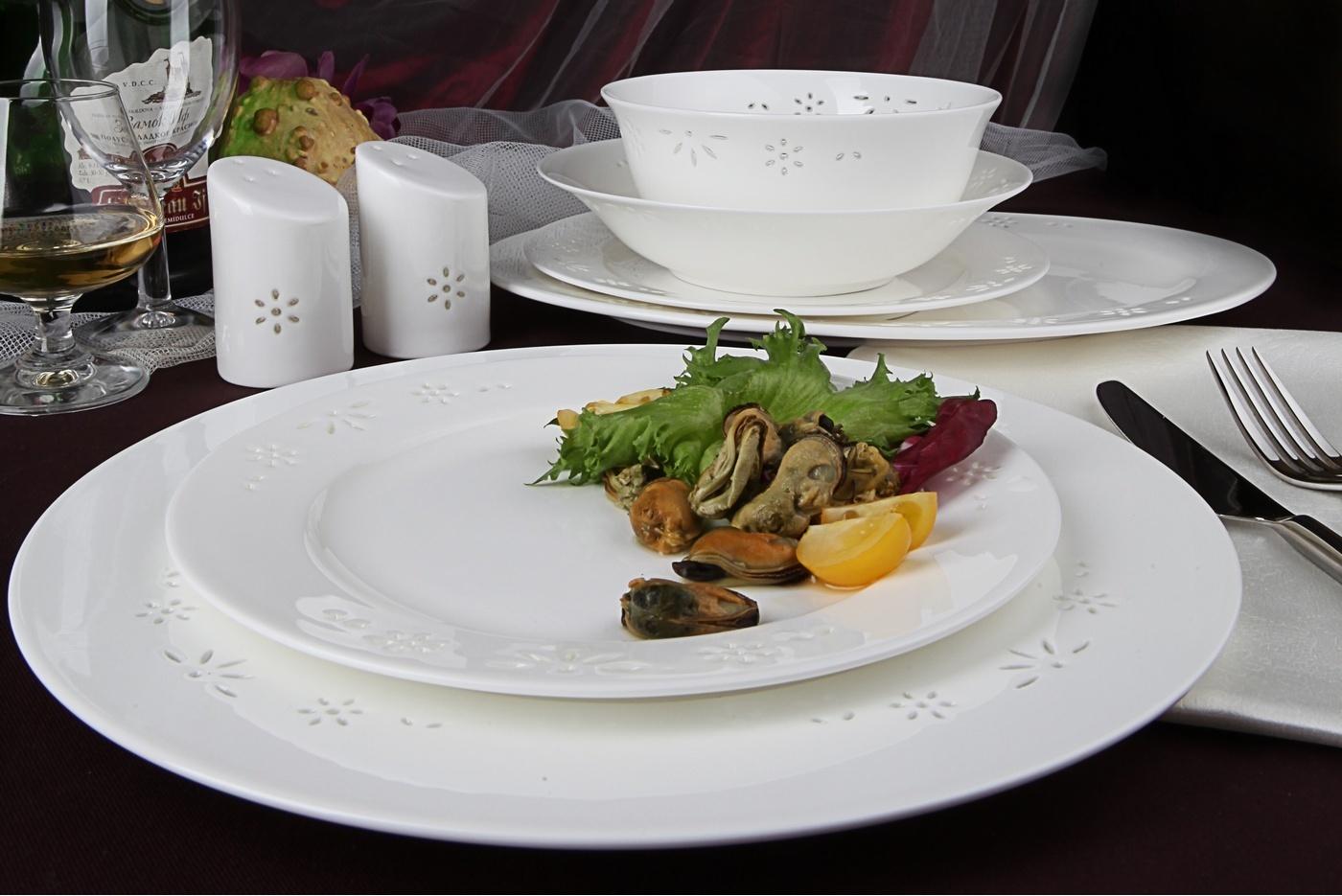 Столовый сервиз Royal Aurel Севилья арт.439, 27 предметовСтоловые сервизы<br>Столовый сервиз Royal Aurel Севилья арт.439, 27 предметов<br><br><br><br><br><br><br><br><br><br><br><br>Тарелка плоская 27 см, 6 шт.<br>Тарелка плоская 20 см, 6 шт.<br>Тарелка суповая 19,5 см, 6 шт.<br>Салатник 15 см, 6 шт.<br><br><br><br><br><br><br><br><br>Блюдо овальное 31см<br>Солонка и перечница<br><br><br><br><br><br><br><br>Производить посуду из фарфора начали в Китае на стыке 6-7 веков. Неустанно совершенствуя и селективно отбирая сырье для производства посуды из фарфора, мастерам удалось добиться выдающихся характеристик фарфора: белизны и тонкостенности. В XV веке появился особый интерес к китайской фарфоровой посуде, так как в это время Европе возникла мода на самобытные китайские вещи. Роскошный китайский фарфор являлся изыском и был в новинку, поэтому он выступал в качестве подарка королям, а также знатным людям. Такой дорогой подарок был очень престижен и по праву являлся элитной посудой. Как известно из многочисленных исторических документов, в Европе китайские изделия из фарфора ценились практически как золото. <br>Проверка изделий из костяного фарфора на подлинность <br>По сравнению с производством других видов фарфора процесс производства изделий из настоящего костяного фарфора сложен и весьма длителен. Посуда из изящного фарфора - это элитная посуда, которая всегда ассоциируется с богатством, величием и благородством. Несмотря на небольшую толщину, фарфоровая посуда - это очень прочное изделие. Для демонстрации плотности и прочности фарфора можно легко коснуться предметов посуды из фарфора деревянной палочкой, и тогда мы услушим характерный металлический звон. В составе фарфоровой посуды присутствует костяная зола, благодаря чему она может быть намного тоньше (не более 2,5 мм) и легче твердого или мягкого фарфора. Безупречная белизна - ключевой признак отличия такого фарфора от других. Цвет обычного фарфора сероватый или ближе к голубоватому, а костяной фарфор будет всег