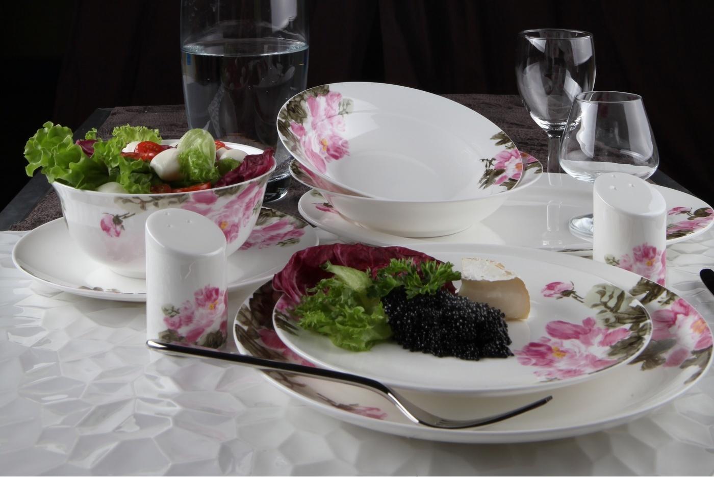 Столовый сервиз Royal Aurel Дикая роза арт.440, 27 предметовСтоловые сервизы<br>Столовый сервиз Royal Aurel Дикая роза арт.440, 27 предметов<br><br><br><br><br><br><br><br><br><br><br><br>Тарелка плоская 25 см, 6 шт.<br>Тарелка плоская 20 см, 6 шт.<br>Тарелка суповая 19,5 см, 6 шт.<br>Салатник 15 см, 6 шт.<br><br><br><br><br><br><br><br><br>Блюдо овальное 31см<br>Солонка и перечница<br><br><br><br><br><br><br><br>Производить посуду из фарфора начали в Китае на стыке 6-7 веков. Неустанно совершенствуя и селективно отбирая сырье для производства посуды из фарфора, мастерам удалось добиться выдающихся характеристик фарфора: белизны и тонкостенности. В XV веке появился особый интерес к китайской фарфоровой посуде, так как в это время Европе возникла мода на самобытные китайские вещи. Роскошный китайский фарфор являлся изыском и был в новинку, поэтому он выступал в качестве подарка королям, а также знатным людям. Такой дорогой подарок был очень престижен и по праву являлся элитной посудой. Как известно из многочисленных исторических документов, в Европе китайские изделия из фарфора ценились практически как золото. <br>Проверка изделий из костяного фарфора на подлинность <br>По сравнению с производством других видов фарфора процесс производства изделий из настоящего костяного фарфора сложен и весьма длителен. Посуда из изящного фарфора - это элитная посуда, которая всегда ассоциируется с богатством, величием и благородством. Несмотря на небольшую толщину, фарфоровая посуда - это очень прочное изделие. Для демонстрации плотности и прочности фарфора можно легко коснуться предметов посуды из фарфора деревянной палочкой, и тогда мы услушим характерный металлический звон. В составе фарфоровой посуды присутствует костяная зола, благодаря чему она может быть намного тоньше (не более 2,5 мм) и легче твердого или мягкого фарфора. Безупречная белизна - ключевой признак отличия такого фарфора от других. Цвет обычного фарфора сероватый или ближе к голубоватому, а костяной фарфор буде