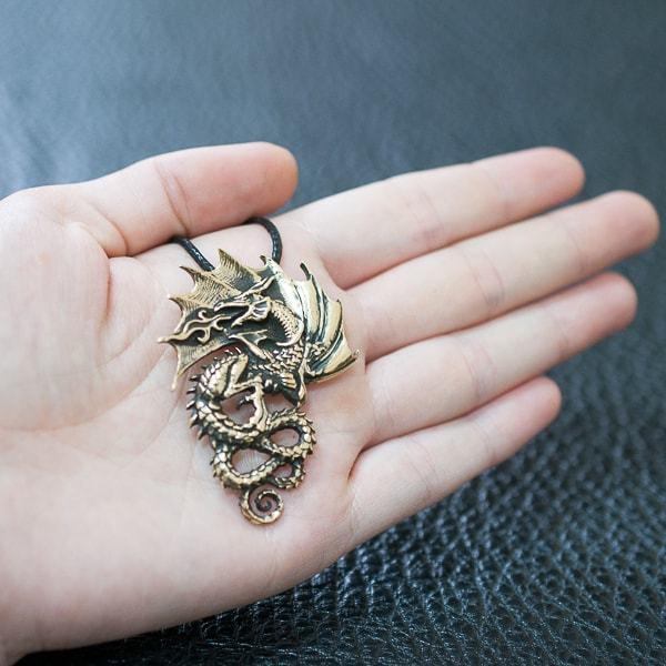 Кулон Восточный дракон лежит на руке.