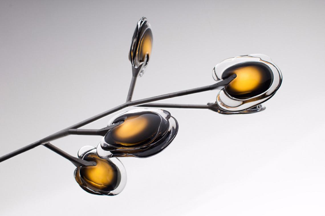 Серия 16. Три слоя жидкого цветного стекла последовательно выливаются на горизонтальную поверхность. Поскольку формы у таких фигур получаются расплывчатыми и неправильными, каждый плафон обладает уникальной комбинацией цветовых пятен. Просвечивающиеся слои стекла рождают интересные эффекты. Модульная арматура из сегментов позволяет создавать разнообразные композиции: можно даже собрать светильник в качестве настольной лампы или торшера. Представлены три цвета арматуры – тертый алюминий, покрытие латунью или же белый цвет.