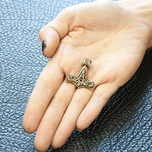 Бронзовый кулон молот Тора, фотография на руке.