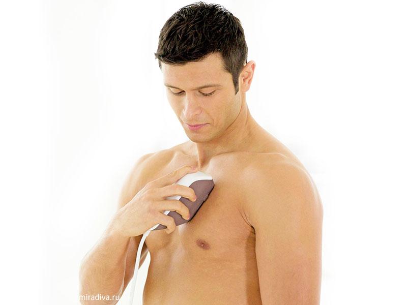 Мужчина удаляет волосы на груди при помощи фотоэпилятора