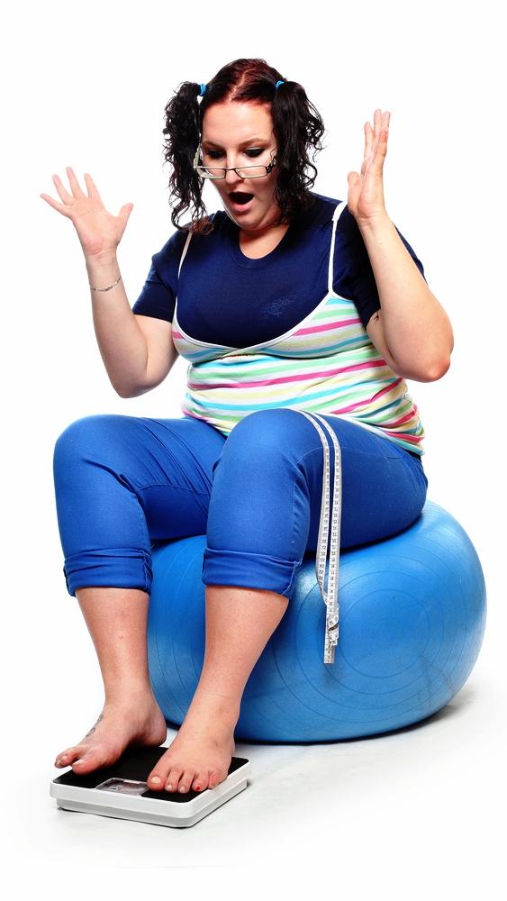 Женщина измеряет свой свой вес, и думает как похудеть сидя на фитболе