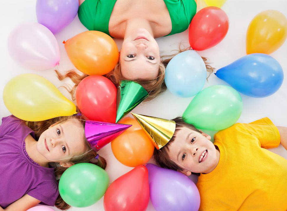children-and-adult-wearing-birthday-hats-near-balloons.jpg