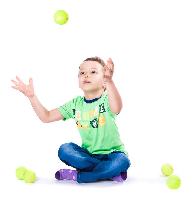 Мальчик подбрасывает и ловит теннисный мяч