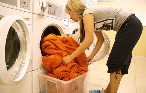 женщина стирает чехол тканевого шкафа в стиральной машинке