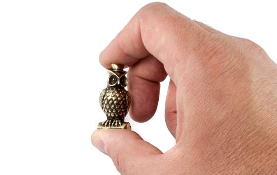 Фотография фигруки совы в шляпе в руке, для масштаба