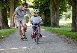 Папа учит ребенка держать кататься на велосипеде
