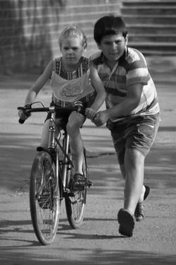 Брат учит сестру кататься на велосипеде