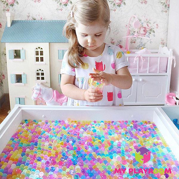 Девочка играет с гидрогелем на световом столе
