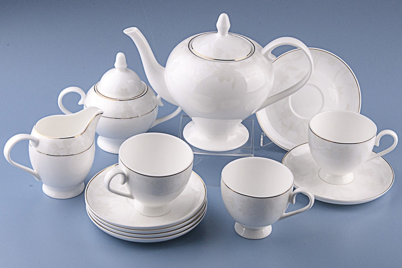 Чайный сервиз Royal Aurel Белый лотос арт.109, 15 предметовЧайные сервизы<br>Чайный сервиз Royal Aurel Белый лотос арт.109, 15 предметов<br><br><br><br><br><br><br><br><br><br><br>Чашка 270 мл,6 шт.<br>Блюдце 15 см,6 шт.<br>Чайник 1100 мл<br>Сахарница 370 мл<br><br><br><br><br><br><br><br><br>Молочник 300 мл<br><br><br><br><br><br><br><br><br>Производить посуду из фарфора начали в Китае на стыке 6-7 веков. Неустанно совершенствуя и селективно отбирая сырье для производства посуды из фарфора, мастерам удалось добиться выдающихся характеристик фарфора: белизны и тонкостенности. В XV веке появился особый интерес к китайской фарфоровой посуде, так как в это время Европе возникла мода на самобытные китайские вещи. Роскошный китайский фарфор являлся изыском и был в новинку, поэтому он выступал в качестве подарка королям, а также знатным людям. Такой дорогой подарок был очень престижен и по праву являлся элитной посудой. Как известно из многочисленных исторических документов, в Европе китайские изделия из фарфора ценились практически как золото. <br>Проверка изделий из костяного фарфора на подлинность <br>По сравнению с производством других видов фарфора процесс производства изделий из настоящего костяного фарфора сложен и весьма длителен. Посуда из изящного фарфора - это элитная посуда, которая всегда ассоциируется с богатством, величием и благородством. Несмотря на небольшую толщину, фарфоровая посуда - это очень прочное изделие. Для демонстрации плотности и прочности фарфора можно легко коснуться предметов посуды из фарфора деревянной палочкой, и тогда мы услушим характерный металлический звон. В составе фарфоровой посуды присутствует костяная зола, благодаря чему она может быть намного тоньше (не более 2,5 мм) и легче твердого или мягкого фарфора. Безупречная белизна - ключевой признак отличия такого фарфора от других. Цвет обычного фарфора сероватый или ближе к голубоватому, а костяной фарфор будет всегда будет молочно-белого цвета. Характерная и немаловажная деталь -