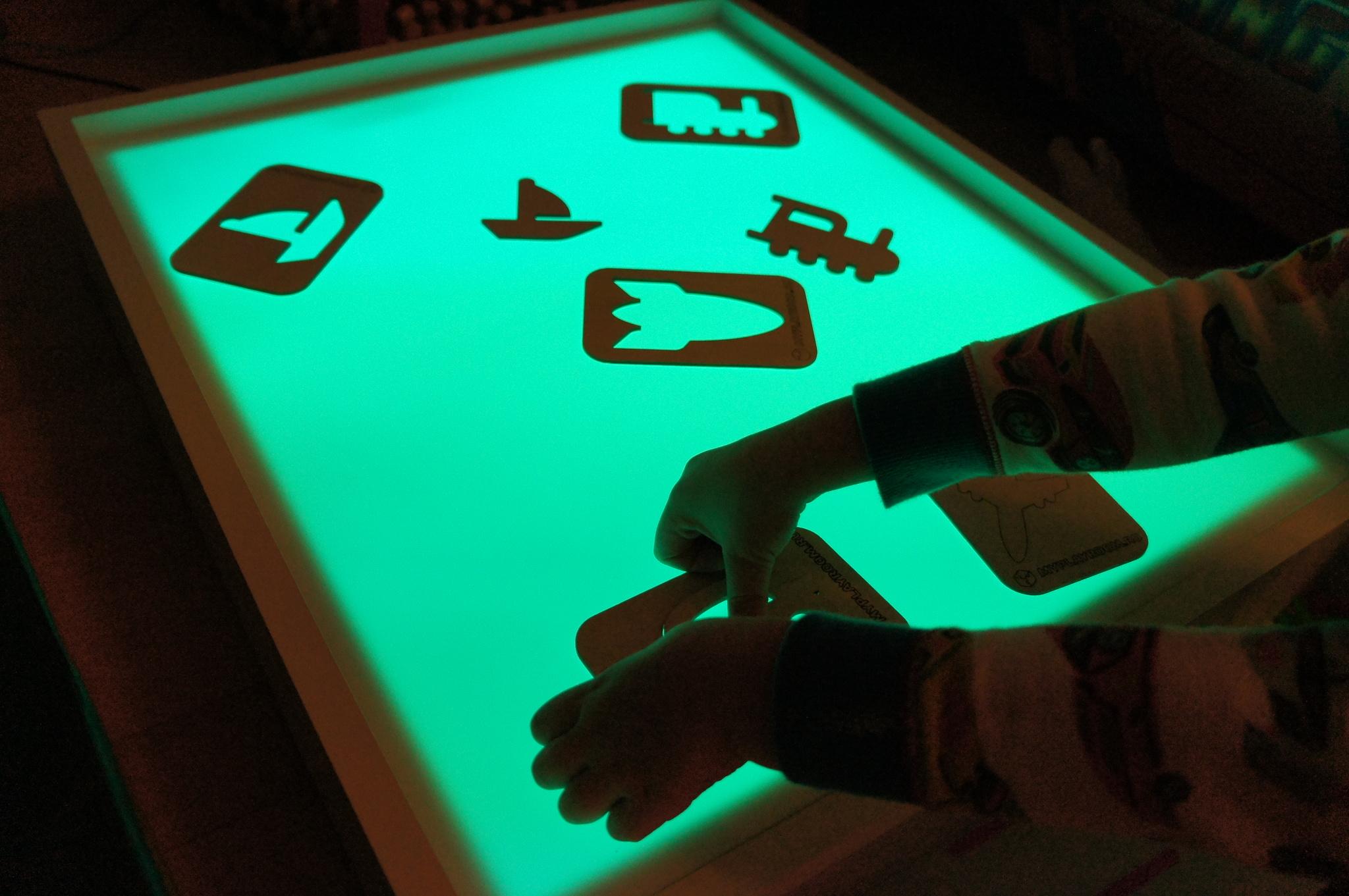 Ребёнок вкладывает трафареты ТРАНСПОРТ в рамки на световом столике Myplayroom.ru