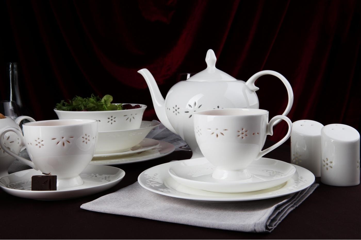 Чайный сервиз Royal Aurel Севилья арт.139, 15 предметовЧайные сервизы<br>Чайныйсервиз Royal Aurel Севилья арт.139, 15предметов<br><br><br><br><br><br><br><br><br><br><br><br>Чашка 270 мл,6 шт.<br>Блюдце 15 см,6 шт.<br>Чайник 1100 мл<br>Сахарница 370 мл<br><br><br><br><br><br><br><br><br>Молочник 300 мл<br><br><br><br><br><br><br><br><br>Производить посуду из фарфора начали в Китае на стыке 6-7 веков. Неустанно совершенствуя и селективно отбирая сырье для производства посуды из фарфора, мастерам удалось добиться выдающихся характеристик фарфора: белизны и тонкостенности. В XV веке появился особый интерес к китайской фарфоровой посуде, так как в это время Европе возникла мода на самобытные китайские вещи. Роскошный китайский фарфор являлся изыском и был в новинку, поэтому он выступал в качестве подарка королям, а также знатным людям. Такой дорогой подарок был очень престижен и по праву являлся элитной посудой. Как известно из многочисленных исторических документов, в Европе китайские изделия из фарфора ценились практически как золото. <br>Проверка изделий из костяного фарфора на подлинность <br>По сравнению с производством других видов фарфора процесс производства изделий из настоящего костяного фарфора сложен и весьма длителен. Посуда из изящного фарфора - это элитная посуда, которая всегда ассоциируется с богатством, величием и благородством. Несмотря на небольшую толщину, фарфоровая посуда - это очень прочное изделие. Для демонстрации плотности и прочности фарфора можно легко коснуться предметов посуды из фарфора деревянной палочкой, и тогда мы услушим характерный металлический звон. В составе фарфоровой посуды присутствует костяная зола, благодаря чему она может быть намного тоньше (не более 2,5 мм) и легче твердого или мягкого фарфора. Безупречная белизна - ключевой признак отличия такого фарфора от других. Цвет обычного фарфора сероватый или ближе к голубоватому, а костяной фарфор будет всегда будет молочно-белого цвета. Характерная и немаловажная деталь - это н